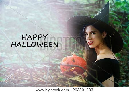 Young Pretty Woman In Witch's Hat Holding Halloween Pumpkin Jack