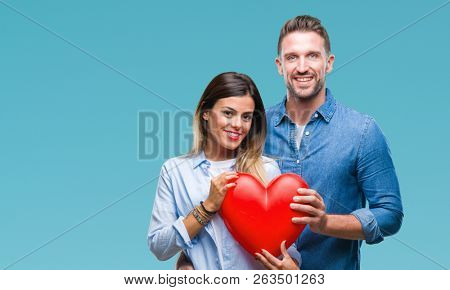 Young couple in love holding red heart over isolated background with a happy face standing and smiling with a confident smile showing teeth