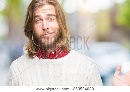 Young handsome man with long hair wearing winter sweater over isolated background clueless and confused expression with arms and hands raised. Doubt concept.