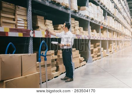 Wholesale, Logistic, Business, Export And People Concept - Man Warehouse Worker Checking Goods At Wa