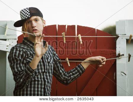 Teenage Boy Leaning On A Clothesline