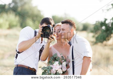 Wedding Photographer Takes Pictures Of Bride And Groom