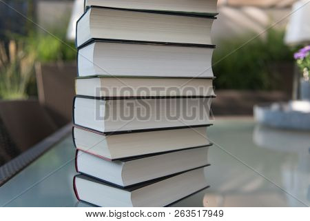Several Books As A Stack On A Glass Table