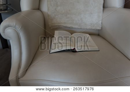 Open Book Lies On A Leather Chair