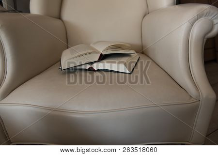 Two Open Books On A Leather Chair