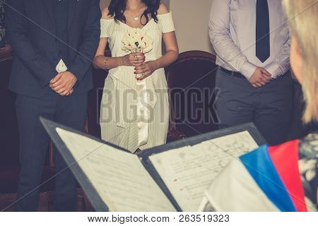 Marriage Registrar Reading Marriage Contract In Civil Registry Office. Selective Focus On Bride And