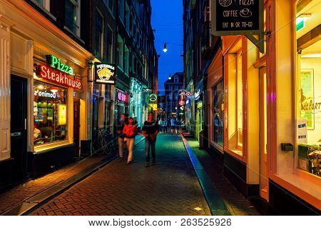 AMSTERDAM, NETHERLANDS - JULY 07, 2015: People passing by illuminated shops, restaurants and bars in old historic part of Amsterdam - capital of Netherlands, famous and popular travel destination.
