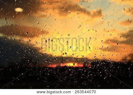 Rain Outside Window On Background Of Sunset. Rain Drops On Glass During Rain. Sunset Outside Window