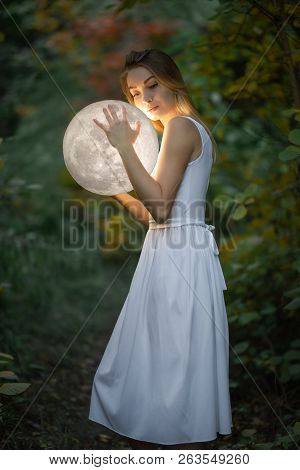 Beautiful Attractive Girl In A White Dress In The Autumn Forest, Hugs The Moon, A Mystery, A Mysteri