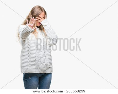 Beautiful young blonde woman wearing winter sweater over isolated background covering eyes with hands and doing stop gesture with sad and fear expression. Embarrassed and negative concept. poster