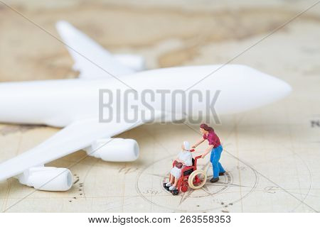 Medical trip planning or travel concept, miniature senior elderly people on wheelchair with son or caregiver standing with toy airplane on vintage world map with compass, next destination. poster