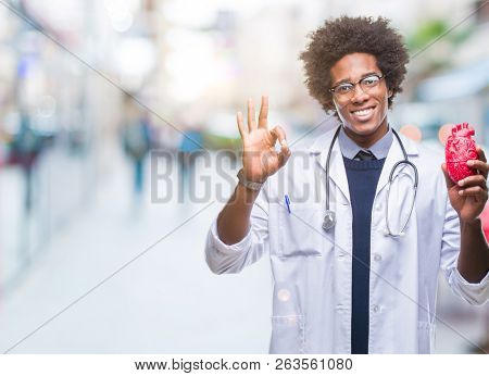 Afro american cardiologist doctor man over isolated background doing ok sign with fingers, excellent symbol