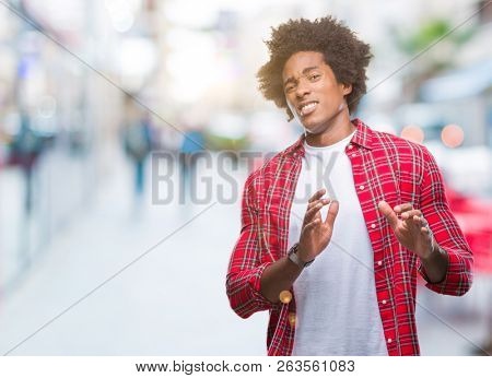 Afro american man over isolated background disgusted expression, displeased and fearful doing disgust face because aversion reaction. With hands raised. Annoying concept.