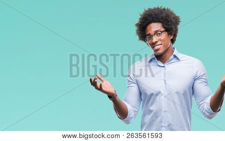 Afro american business man wearing glasses over isolated background clueless and confused expression with arms and hands raised. Doubt concept.