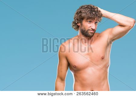 Handsome hispanic model man sexy and shirtless over isolated background confuse and wonder about question. Uncertain with doubt, thinking with hand on head. Pensive concept.