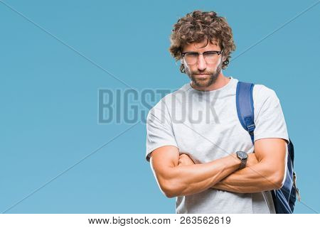 Handsome hispanic student man wearing backpack and glasses over isolated background skeptic and nervous, disapproving expression on face with crossed arms. Negative person. poster