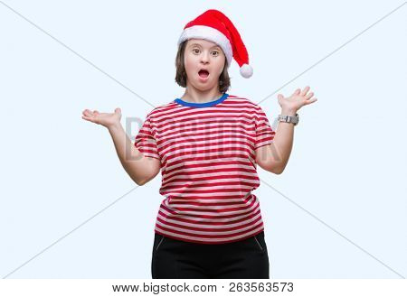 Young adult woman with down syndrome wearing christmas hat over isolated background clueless and confused expression with arms and hands raised. Doubt concept.