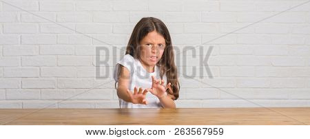 Young hispanic kid sitting on the table at home disgusted expression, displeased and fearful doing disgust face because aversion reaction. With hands raised. Annoying concept.