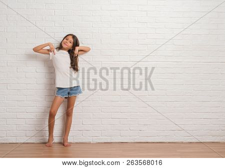 Young hispanic kid stading over white brick wall looking confident with smile on face, pointing oneself with fingers proud and happy.