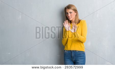 Beautiful young woman standing over grunge grey wall disgusted expression, displeased and fearful doing disgust face because aversion reaction. With hands raised. Annoying concept.