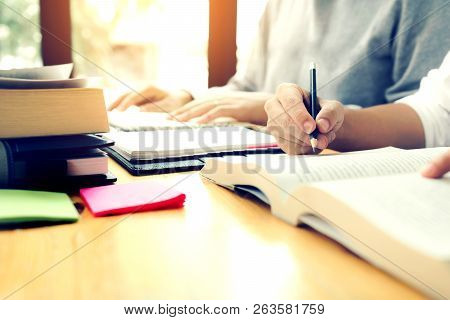 Teenage Student Works On Homework In His Room And Writing In Notebook.