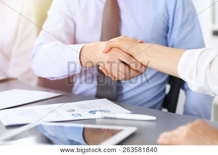 Close-up Of Business Handshake At Meeting Or Negotiation Above The Desk In Office. Partners Shaking