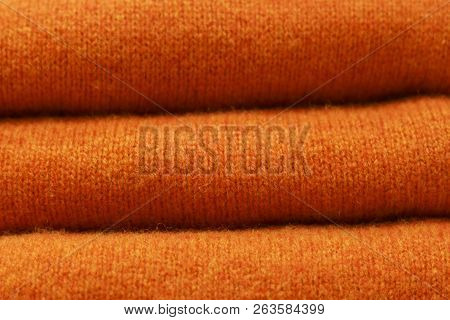 Stack Of Trend Russet Orange Woolen Sweaters Close-up, Texture, Background