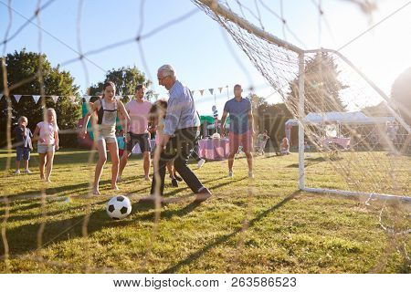 Children Playing Football Match With Father And Grandfather At Summer Garden Fete