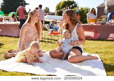 Two Mothers With Babies On Rug At Summer Garden Fete