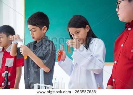 Young Asian Schoolgirl Pouring Chemical Liquid In Classroom