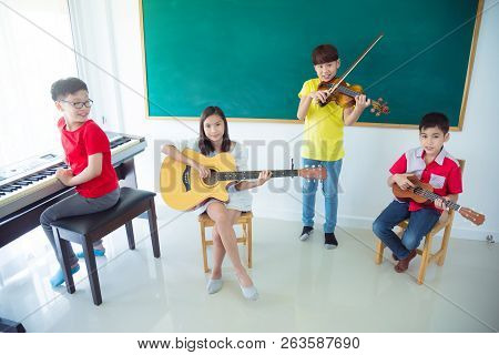 Group Of Happy Asian Kids Playing Music Instruments And Smile In School Classroom