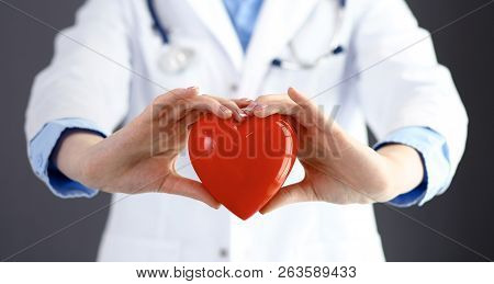 Female Doctor With Stethoscope Holding Heart In Her Arms. Healthcare And Cardiology Concept  In Medi