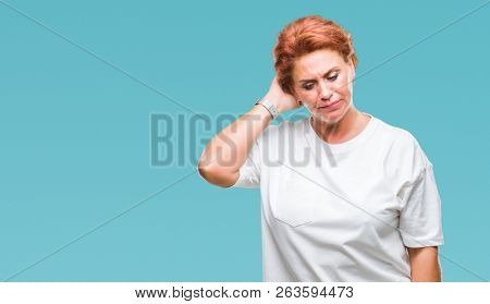 Atrractive senior caucasian redhead woman over isolated background confuse and wonder about question. Uncertain with doubt, thinking with hand on head. Pensive concept.
