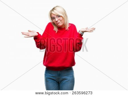 Young beautiful blonde woman wearing sweater and glasses over isolated background clueless and confused expression with arms and hands raised. Doubt concept.