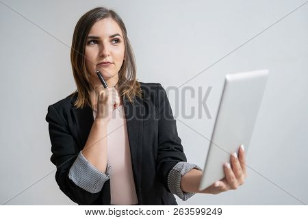 Pensive Young Caucasian Woman Holding Tablet And Pen. Portrait Of Pretty Dark-haired Businesswoman C