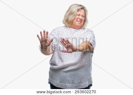 Senior plus size caucasian woman over isolated background disgusted expression, displeased and fearful doing disgust face because aversion reaction. With hands raised. Annoying concept.