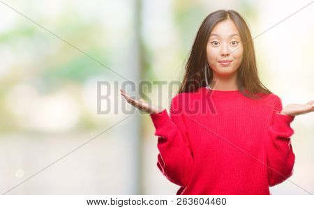 Young asian woman wearing winter sweater over isolated background clueless and confused expression with arms and hands raised. Doubt concept.