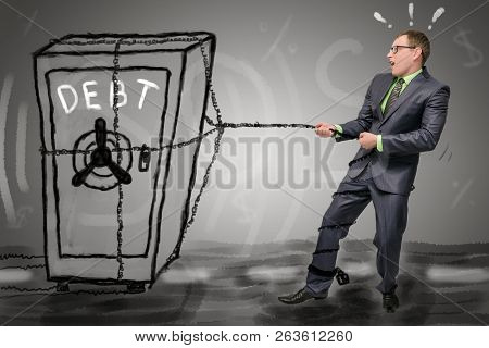 Debts concept. Businessman is dragging along the road a safe with accumulated debts. No money to pay bills. poster