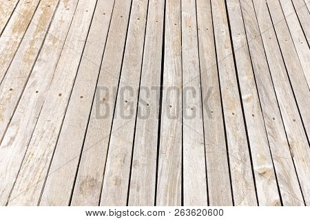 A Close Up View Of Wooden Floor Slates That Have Been Discoloured From Being Out In The Harsh Sun