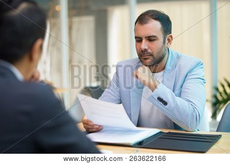 Pensive Hispanic Businessman Reading Contract While Meeting With Business Partner. Concentrated Fina