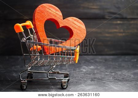 Red Heart In The Supermarket Trolley. Concept Of Buying Love. Valentine's Day. Yellow Background. Lo