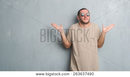 Young caucasian man over grey grunge wall wearing sunglasses clueless and confused expression with arms and hands raised. Doubt concept.