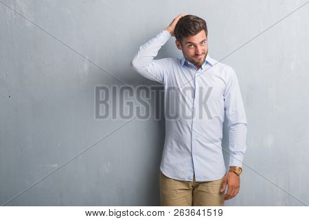 Handsome young business man over grey grunge wall wearing elegant shirt confuse and wonder about question. Uncertain with doubt, thinking with hand on head. Pensive concept.