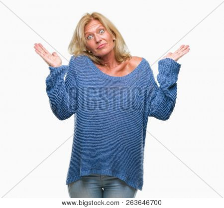 Middle age blonde woman wearing winter sweater over isolated background clueless and confused expression with arms and hands raised. Doubt concept.
