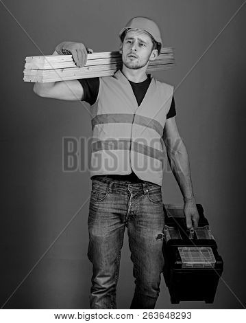 Man, Handyman In Helmet, Hard Hat Holds Toolbox And Wooden Beams, Grey Background. Carpenter, Woodwo