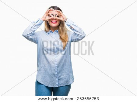 Young beautiful business woman wearing glasses over isolated background doing ok gesture like binoculars sticking tongue out, eyes looking through fingers. Crazy expression.