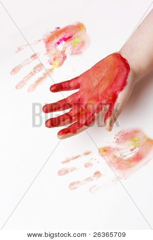 red painted hand and prints of a child ,  playing with colorful paint