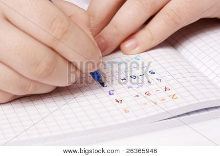 child doing maths homework, adding numbers