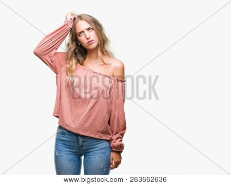 Beautiful young blonde woman over isolated background confuse and wonder about question. Uncertain with doubt, thinking with hand on head. Pensive concept.