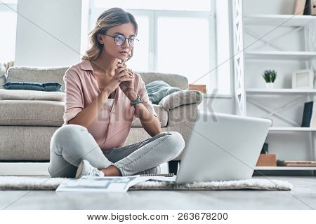 Considering The Next Step. Thoughtful Young Woman In Eyewear Working Using Computer While Flooring A